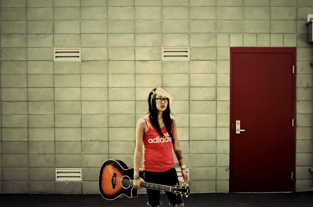 Christine Sako Gray Wall One Hand Holding Guitar
